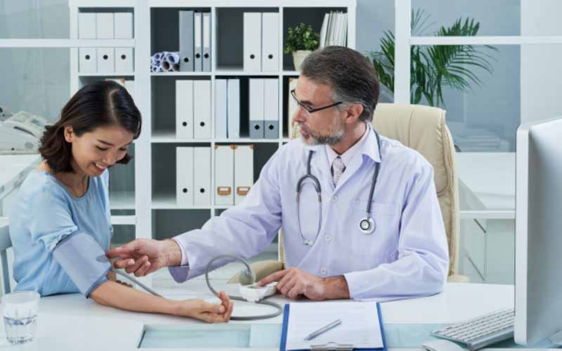 Doctor measuring Blood Pressure of the patient