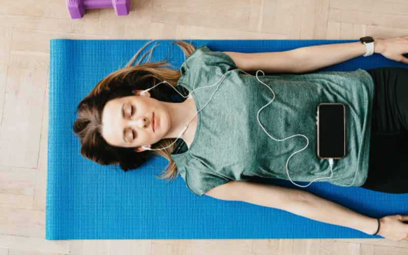 A lady in a resting meditative pose listening to with earphones on