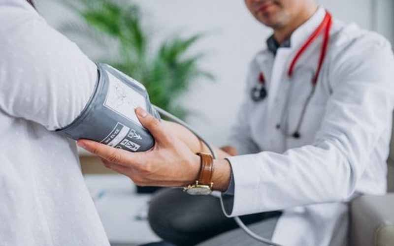 Doctor-holding-patient's-arm-with-a-blood-pressure-monitor