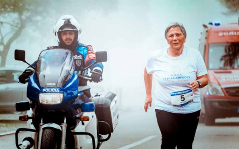 Elderly lady running alongside police motorcycle