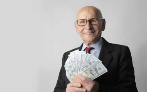 Man in a black suit holding dollar bills