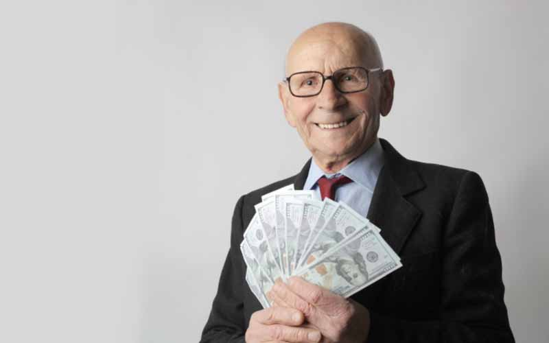 Man in a black suit holding dollar bills