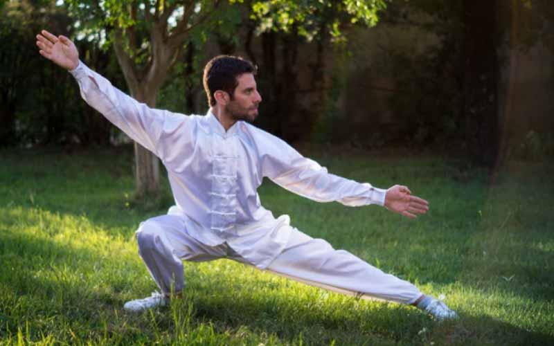Man in white attire in a tai chi pose