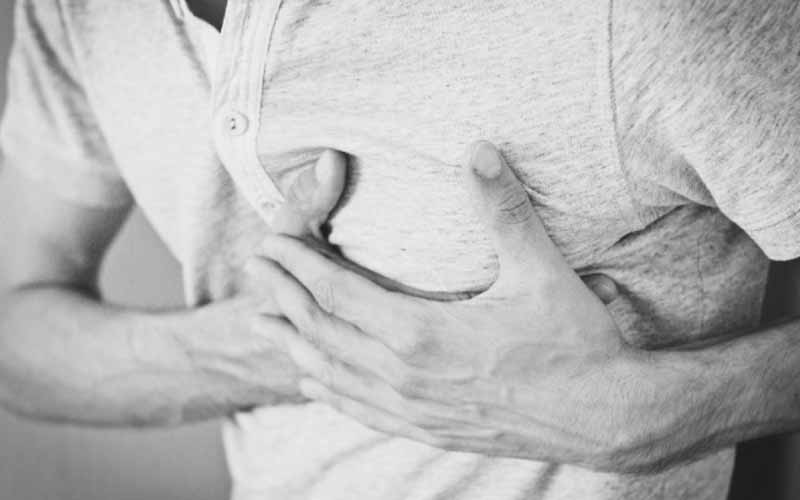 Man suffering from a heart attack and is pressing his chest