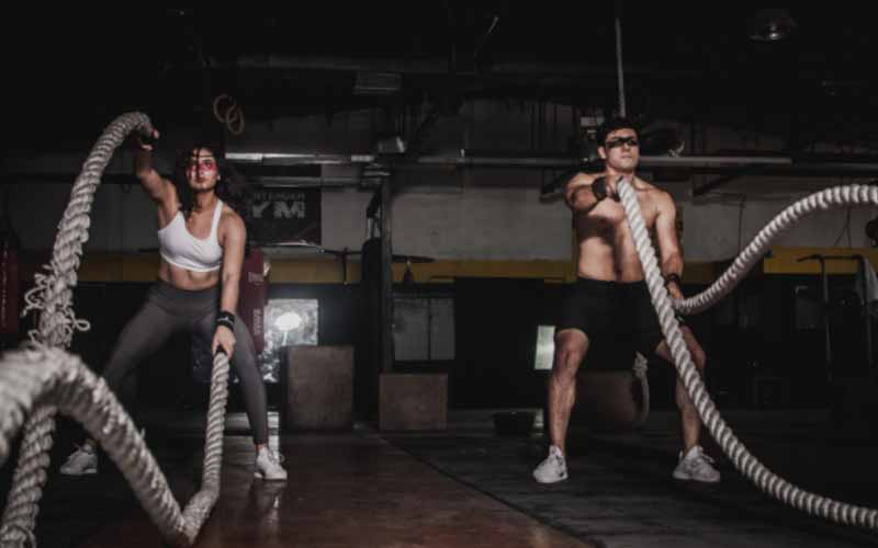 A lady and a man yanking battle ropes