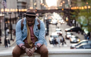 African American man seated in deep thought with traffic in the background