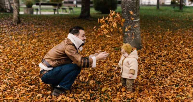 Man playing with a baby in a bed of leaves