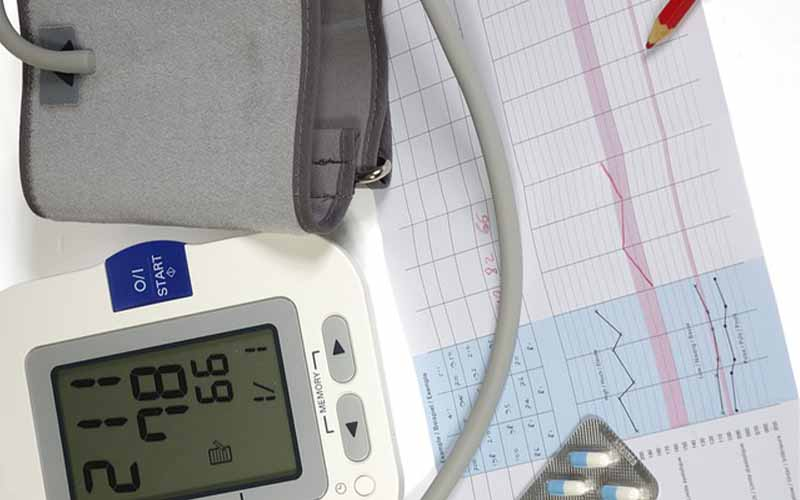 A BP monitor displaying measurements next to a medical chart and pencil