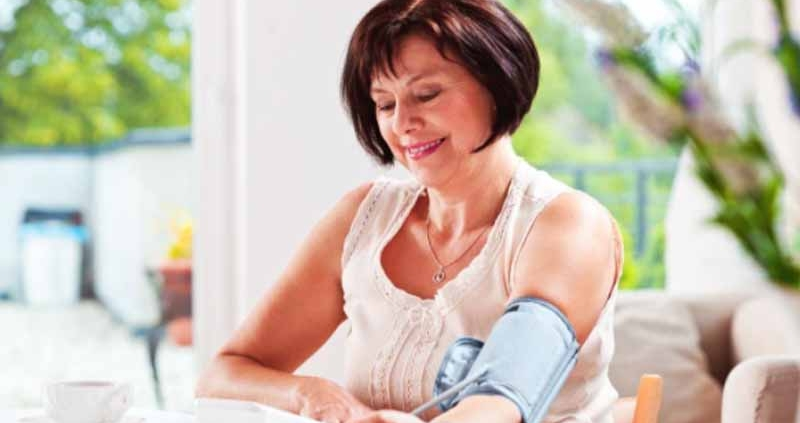 A woman measuring her blood pressure at home