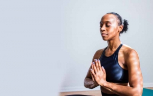 Lady meditating with eyes closed and hands together